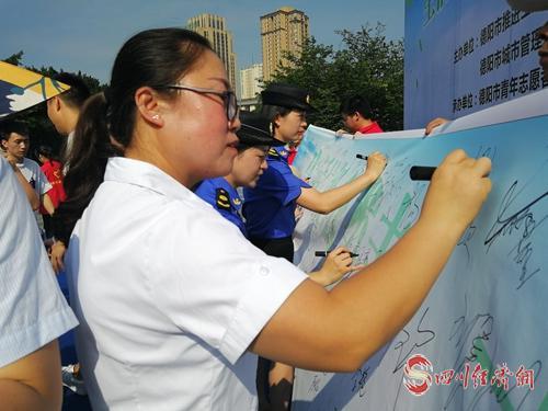 29(29龙 网(0705)刘蓉)德阳市生活垃圾分类志愿服务启动配图    图为志愿者现场签名.jpg