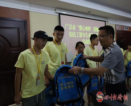 45(网)广汉:开展留守儿童亲情团聚夏令营活动配图    给留守儿童发放书包.jpg