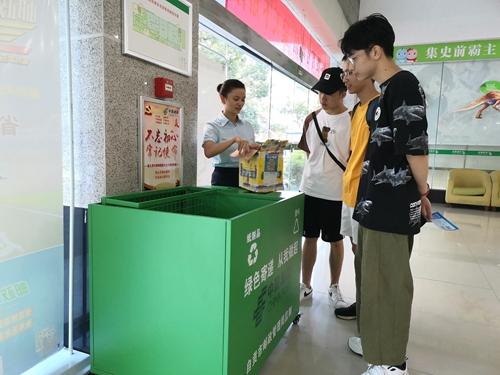 """18(18胡 网 川经瞭望APP 0816 陈家明)践行""""绿色邮政""""理念,用这个分类回收箱可变废为宝配图    图2:工作人员正在向客户介绍快递包裹废弃物收回箱的作用.jpg"""