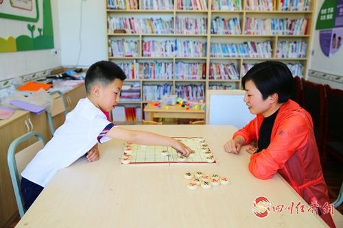 """38(網)丹棱:帶著娃娃去扶貧的第一書記配圖   何君霞帶著兒子值班,在村里的""""農家書屋""""下起了中國象棋。.jpg"""